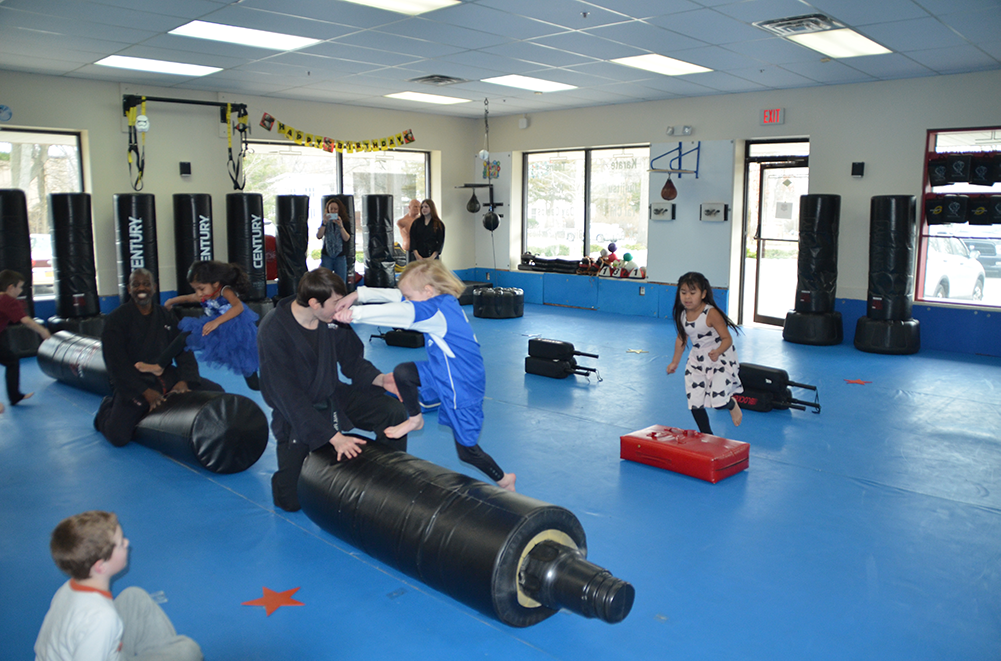 Smiling kids running and jumping as they transverse an obstacle course in a dojo at a Karate Birthday Party