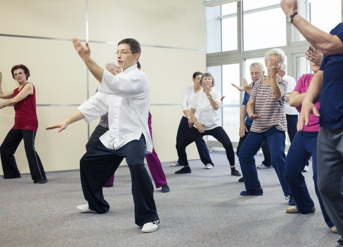 Seniors doing Tai Chi slowly with an instructor