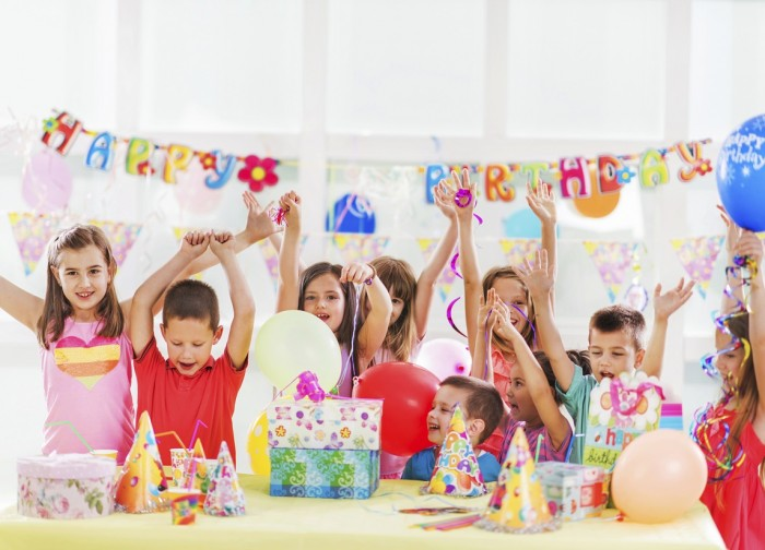 Happy children having fun at birthday party and celebrating with their arms raised.