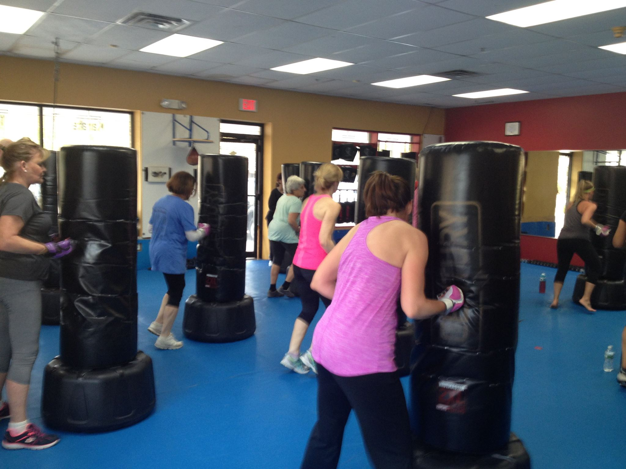 Fitness Kickboxing Women in class uppercutting the bag